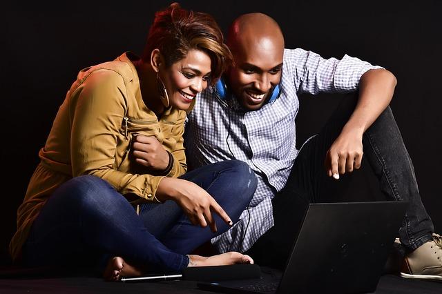 smějící se pár u PC
